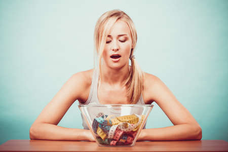 Diet, healthy eating, weight loss and slim body concept. Fit fitness girl and bowl with many colorful measuring tapes, young woman bored of dieting