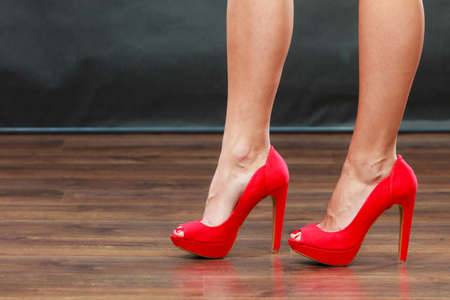 female legs: Female fashion. Closeup red high heels spiked fashionable shoes on female legs Stock Photo