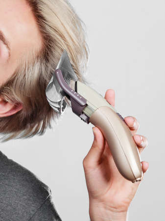 metrosexual: Hairdo hairstyle concept. Cool male hairstylist making self trendy haircut, fashion blonde metrosexual model going to shave his long hair Stock Photo