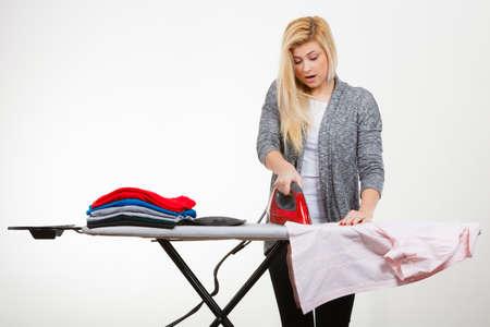 Huisvrouw problemen concept. Geschokte vrouw die zich achter strijkplank bevindt, die partij van te strijken kleren heeft, die een gat branden. Studio die op witte achtergrond is ontsproten Stockfoto