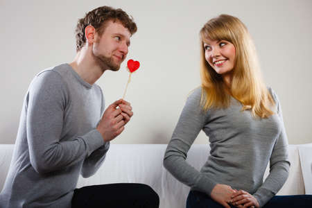 Romance symbolism valentines concept. Man giving heart to his girl. Young male proffesing love to woman, by giving her heart. Stock Photo