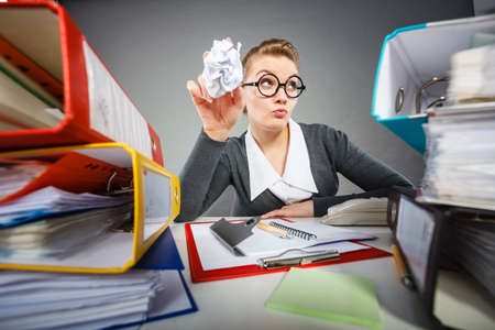tiredness: Boredom and fatigue concept. Young emotional expressive woman in office. Bored tired businesswoman with paper ball at work.