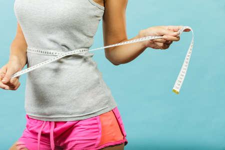 Gewichtsverlies, slank lichaam, gezonde levensstijl concept. Geschiktheid meisje meten haar taille met meetlint op blauw Stockfoto
