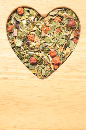 Dried herb leaves heart shaped on wooden surface. Herbaceous dry aromatic plant. Healing herbs herbal medicine concept. Stock Photo