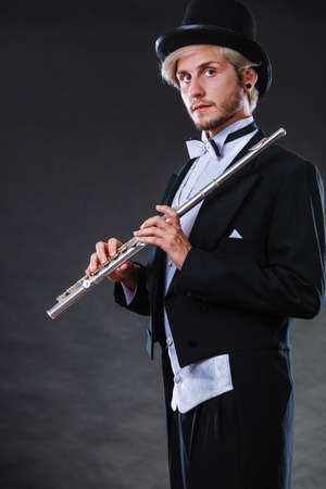 professional flute: Classical music, passion and hobby concept. Elegantly dressed musician man holding flute wearing black hat. Studio shot on dark background