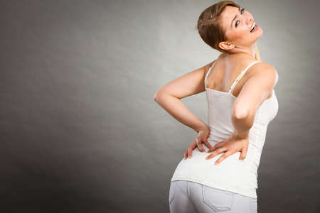 working hours: Long working hours and health. Young female with backache. Woman suffering from back pain on gray