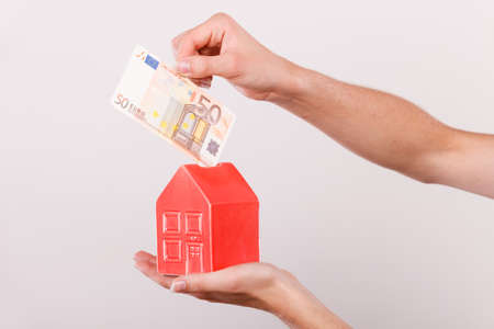Household savings and finances, economy concept. Man putting euro money into a piggy bank in the shape of a house, studio shot on grey background