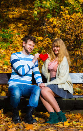 to confess love: Expressing feelings and affection. Confess love with romantic gesture. Young couple sit on bench in park holding plush heart smiling and sharing good emotions. Stock Photo
