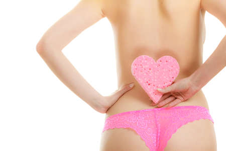 pink panties: Skincare hygiene health and body treatment. Closeup sensual woman wearing pink panties holding heart shaped bath sponge in hand next to hips, isolated on white