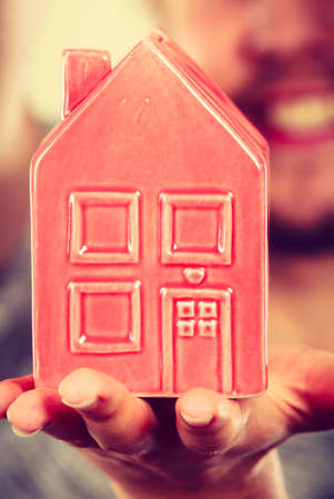 tiny: Household savings, housekeeping concept. Man holding tiny red statue in shape of house. Studio shot on blue background