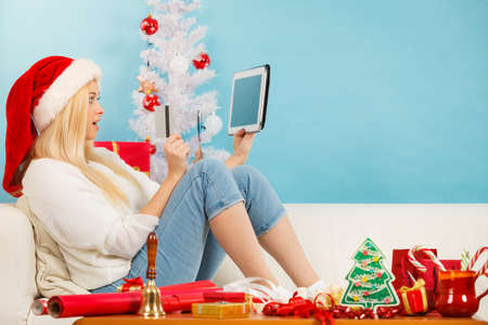 buying time: Christmas time concept. Young woman teen girl with tablet pc laptop and credit card on sofa at home doing online shopping, buying browsing for gifts, having fun