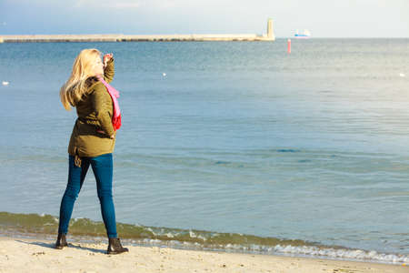 warm jacket: Leisure, spending free time outside, healthy walks concept. Woman wearing warm jacket relaxing on beach near sea, cold sunny day
