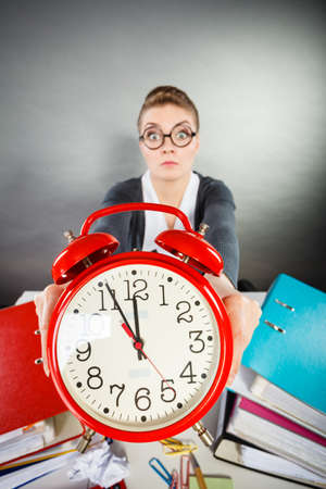 Corporate job workaholism time concept. Emotional secretary with clock. Nervous female office worker at desk with alarm ringer. Stock Photo