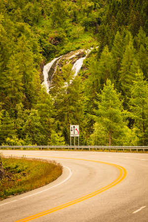 hiils: Road running through norwegian mountains. Beautiful landscape, green hiils with waterfall. Travel and tourism. Stock Photo