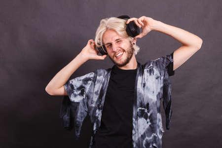 indoor shot: Music, pasion, male artist concept. Blonde man singing in studio wearing big black headphones. Indoor shot on dark grunge background Stock Photo