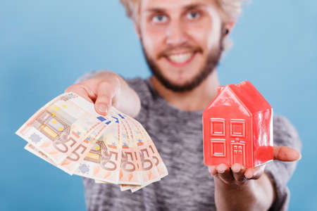 Household savings and finances, economy concept. Smiling man holding money and piggy bank in the shape of a house, studio shot on blue background Stock Photo