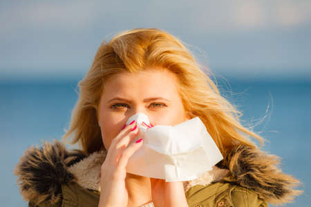 Seasonal flu, cold, runny nose concept. Sneezing blonde young woman into tissue, outside sunny winter shot