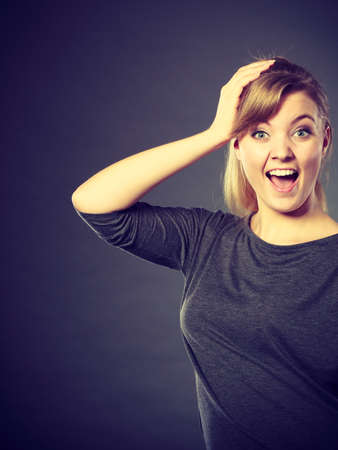 react: Surprise and good shock. Expressive happy charming female portrait. Excited girl with hand on her head showing her stupefaction. Stock Photo