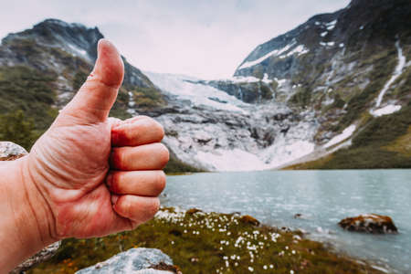 Man hand showing like with thumb up gesture on background of snowy mountains with glacier, approval and travel concept