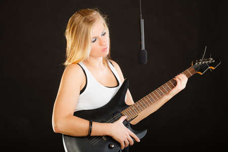 musically: Music, singing concept. Musically talented woman playing on electric guitar and singing in studio, black background