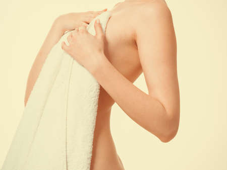 nudity: Shame and fear. Part body woman shamed of her nudity covering her breast with big bath towel. Innocence of female. Stock Photo