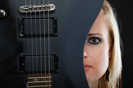 musically: Music, singing concept. Blonde musically talented woman holding electric guitar on black background