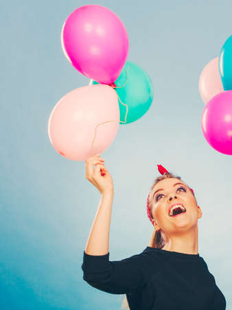 Craziness and lots of fun. Cute crazy joyful girl playing with colored balloons. Blonde playful retro style woman feel craze.