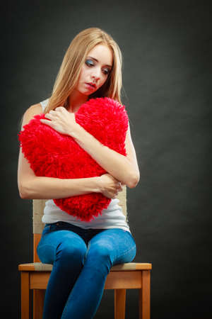 broken chair: Broken heart love concept. Sad unhappy woman sitting on chair hugging red heart pillow dark background