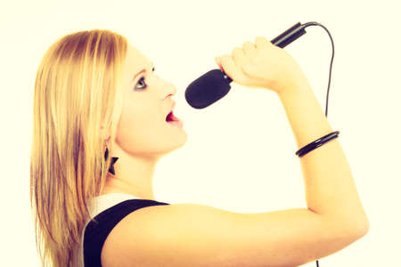audition: Talent and show. Young blonde talented girl showing her passion by singing to microphone. Female singer sing song. Stock Photo
