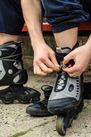 roller blade: Closeup of man guy putting on roller skates outdoor.