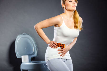 Bellyache, constipation or food poisoning. Woman suffering from strong abdominal pain, holding medical tablets activated carbon in hand, paper on toilet in the background Stock Photo