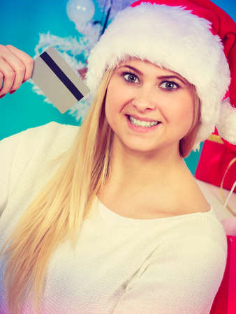 buying time: Christmas time. Young woman teenage girl wearing santa claus hat holding credit card for buying, cozy holiday home interior Stock Photo