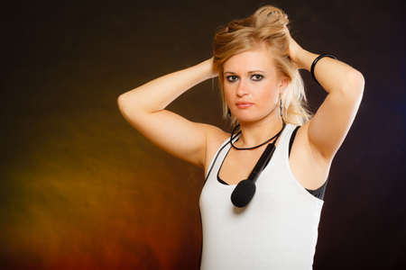 Karaoke, music, singer concept. Blonde woman posing with microphone on shoulder, studio shot. Stock Photo