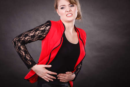 premenstrual syndrome: Sickness and diseases. Health problem concept. Young woman in red holding her hands on stomach belly because of strong terrible bad pain ache.