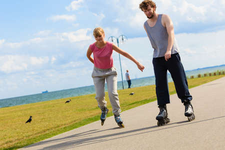 roller blade: Love romance leisure outdoor fitness sport concept. Young pair riding rollerskates in park. Girl and boy together on skates.
