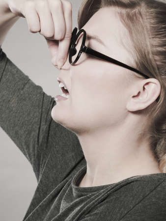 intolerable: Bad smell concept. Young woman feels disgust pinches her nose with fingers because of odor stench unpleasant stink. Facial reaction.