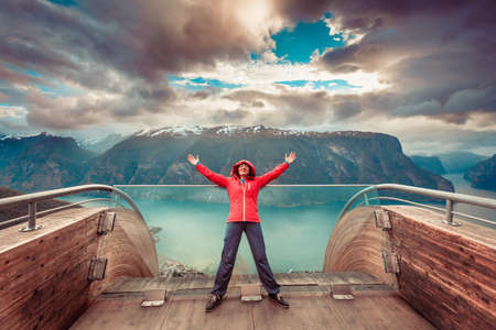 Tourist woman on Stegastein viewpoint enjoying Aurland fjord view with arms raised outstretched up, Sogn Og Fjordane, Norway
