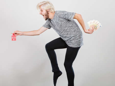 Household savings and finances, economy concept. Happy running man holding money and keys to house, studio shot on grey background Stock Photo