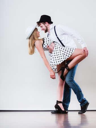 Young happy couple retro style dancing studio shot on gray