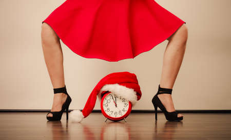 timepiece: Closeup of woman in high heels and alarm clock with santa claus hat. Christmas time season concept. Stock Photo