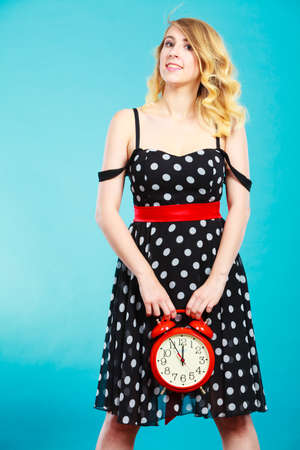 puntualidad: Management time concept. Blonde fashion girl wearing black dotted dress smiling face expression with alarm clock on blue. Foto de archivo