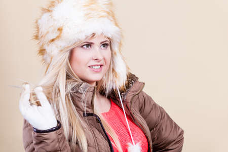 seasonal clothes: Clothing accessories, seasonal clothes concept. Woman wearing jacket and winter furry warm hat Stock Photo