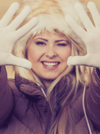 seasonal clothes: Clothing accessories, seasonal clothes concept. Woman wearing jacket and winter furry warm hat gesturing with hands.