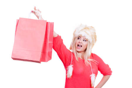 seasonal clothes: Clothing accessories, buying seasonal clothes concept. Woman wearing red jumper and winter furry warm hat holding shopping bags.
