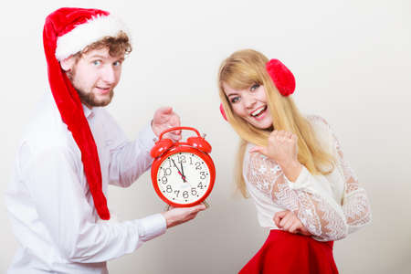 Happy cute couple holding alarm clock. Pretty woman and man in santa claus hat. Christmas time. Stock Photo