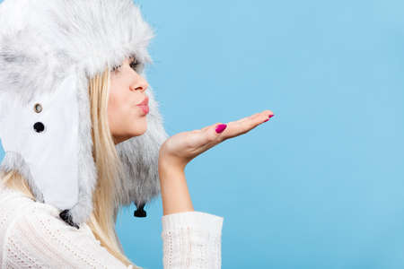 Clothing accessories, seasonal clothes concept. Woman wearing winter furry warm hat sending air kiss. Stock Photo