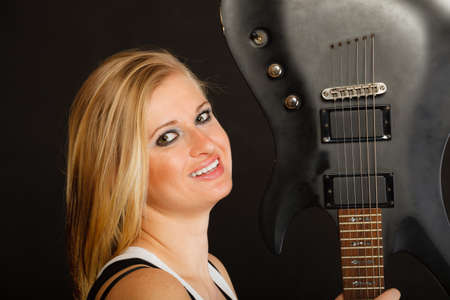 musically: Music, singing concept. Smiling blonde musically talented woman holding electric guitar on black background
