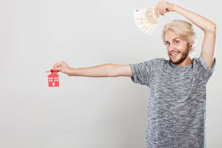 moneyed: Household savings and finances, economy concept. Happy man holding money and keys to house, studio shot on grey background