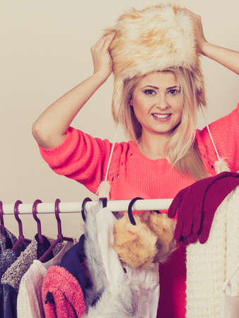 seasonal clothes: Clothing accessories, seasonal clothes concept. Woman wearing winter furry warm hat standing in wardrobe