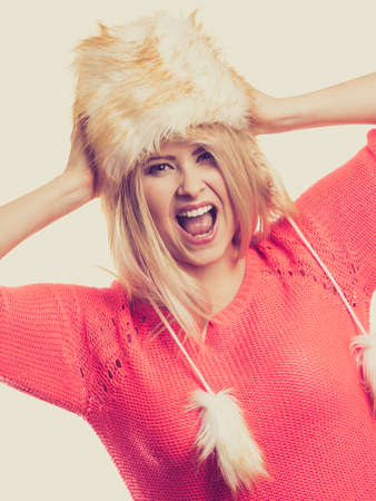 seasonal clothes: Clothing accessories, seasonal clothes concept. Woman wearing red jumper and winter furry warm hat and screaming Stock Photo